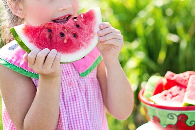 child eating a large piece of watermelon