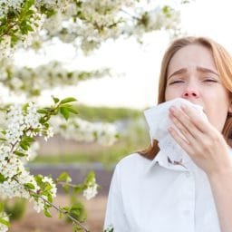 woman in the middle of sneeze with a tissue to her face, outdoors