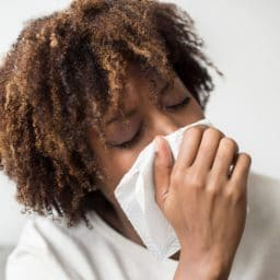 Woman with a tissue to her nose