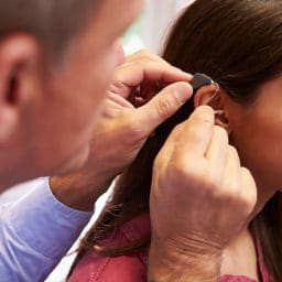 Woman gets hearing aid fitting.