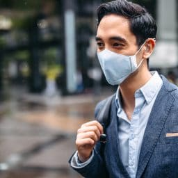Businessman wearing hearing aids and a mask.